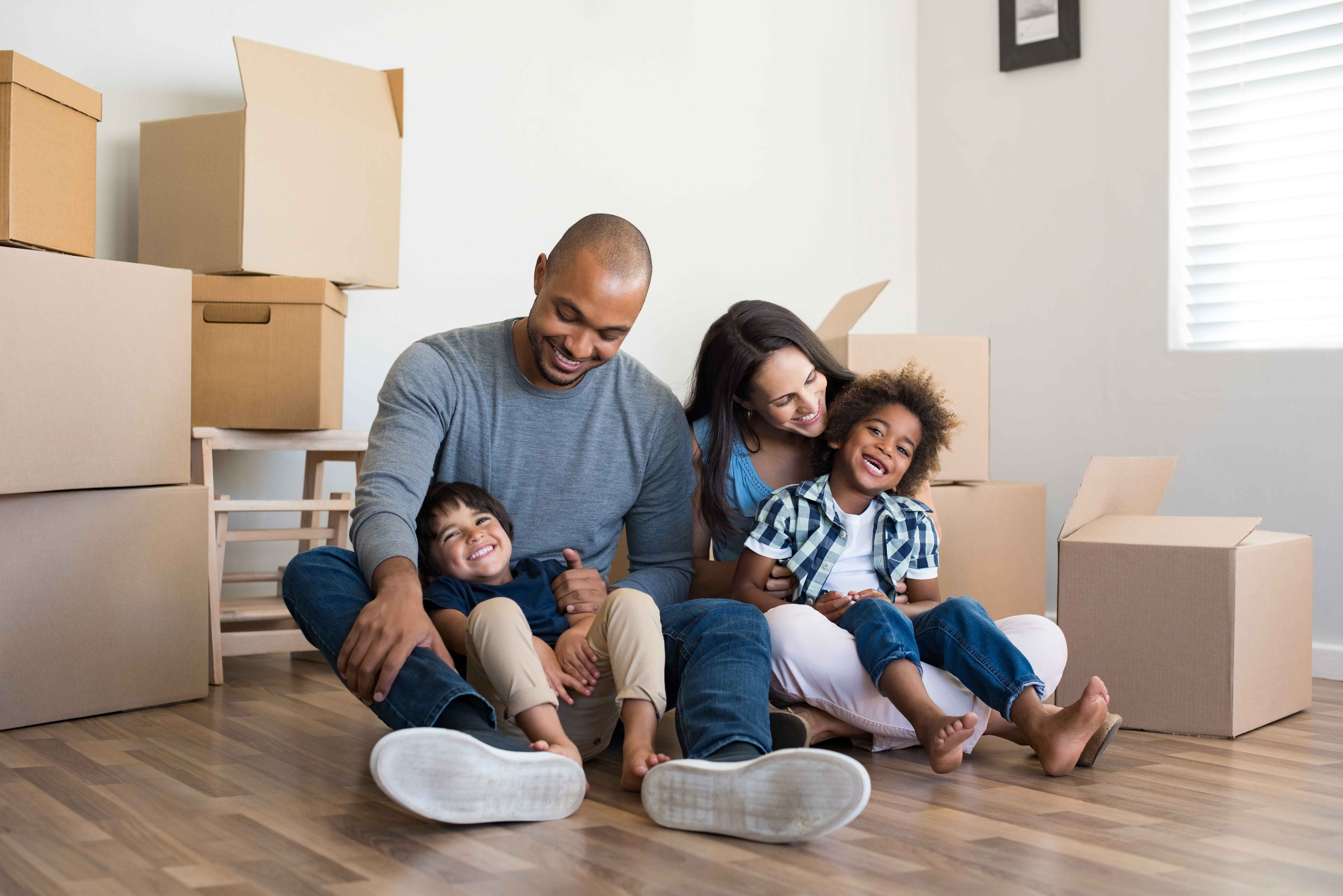 Happy family sitting in a new home with boxes surrounding them