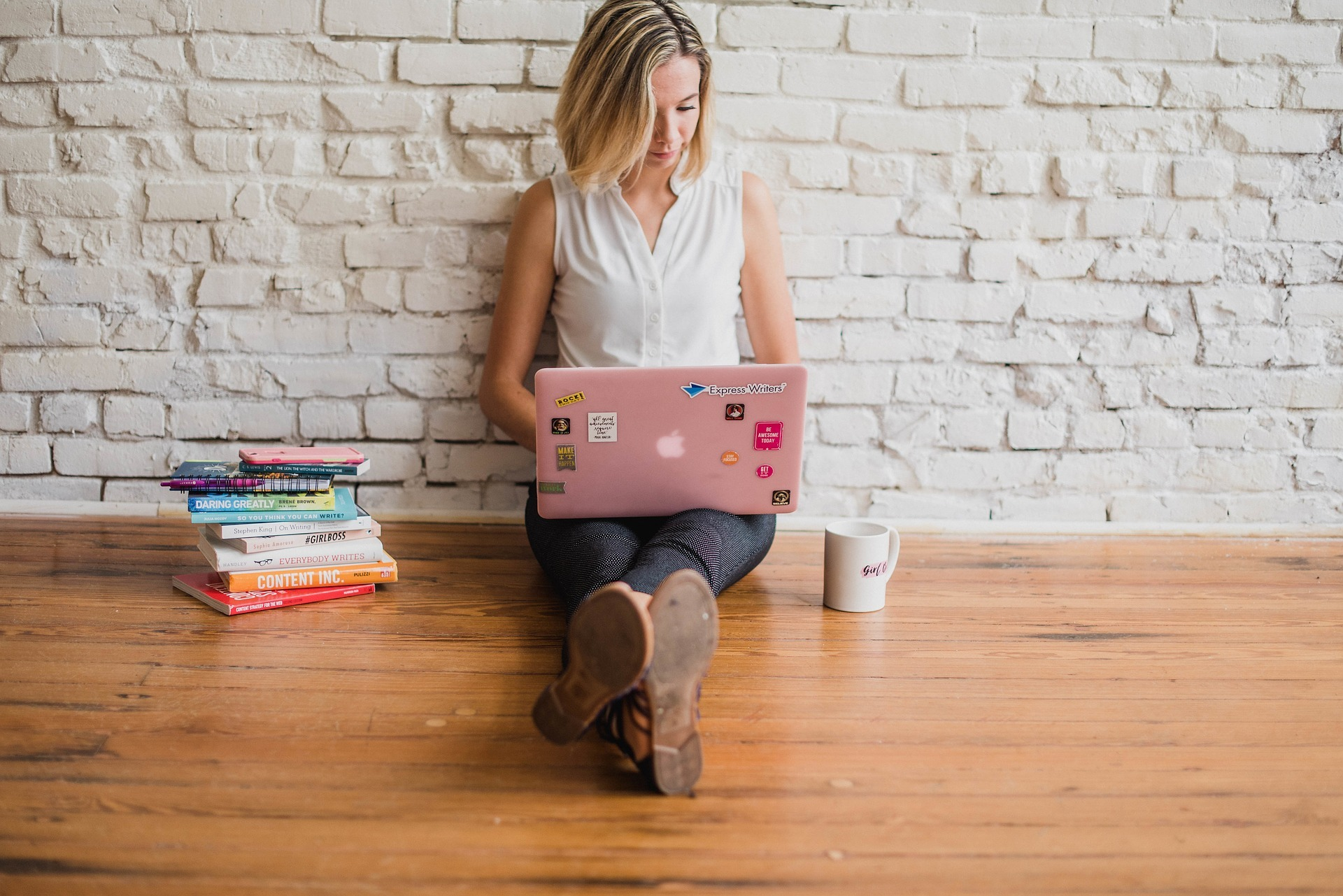 Woman sitting on a hardwood floor. She is using a Macbook with decorative stickers on the cover. To her right is a bile of books and to her left is a coffee mug.