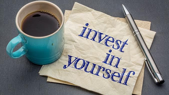 Coffee mug and napkin that reads, invest in yourself.