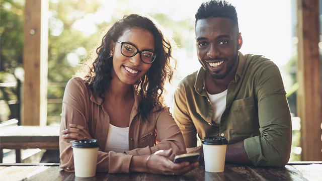 A smiling couple drinking coffee and using mobile phones.